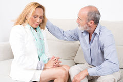 Husband counseling his wife. Elderly men touching the hair of his wife royalty free stock photography