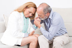 Husband counseling his wife. Elderly men touching the hair of his wife royalty free stock photos