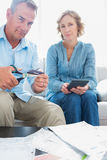 Husband cutting credit card in half with wife with bills on the Stock Photos