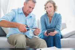 Husband cutting credit card in half with wife looking at camera Royalty Free Stock Photos