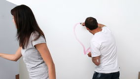 Husband drawing a heart on the wall Royalty Free Stock Images