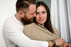 Husband embraces his wife and sheltering blanket royalty free stock images