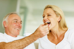 Husband feeding his wife with a piece of chocolate Royalty Free Stock Images