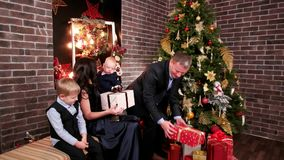 Husband gives gifts to his wife and children, a Christmas party in the family, father mother and baby near Christmas stock video footage
