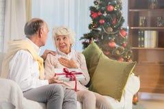 Husband giving christmas gift. Senior husband giving christmas gift box to his wife Royalty Free Stock Images