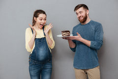 Husband giving plate with chocolae cake to his pregnant wife Royalty Free Stock Photo