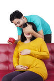 Husband giving a present to his pregnant wife Stock Images