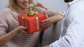 Husband giving present to loving wife, surprise on anniversary of happy marriage. Stock footage stock video