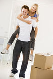 Husband giving wife piggyback in new home smiling royalty free stock photography
