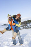 Husband giving wife piggyback ride in snowy field royalty free stock photo