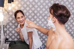 Husband having fun while putting shaving foam on nose of his wife. Foam on nose. Dark-haired husband having fun while putting shaving foam on nose of his cute royalty free stock images