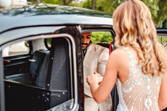 Husband helping bride to enter the car Royalty Free Stock Photo