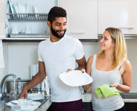 Husband helping girl doing clean up. Afro husband helping white girl doing regular clean up indoors Royalty Free Stock Images