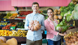 Husband helping girl to choose veggies Stock Photography