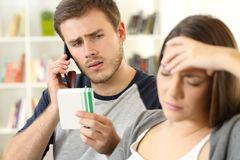Husband helping his sick wife calling doctor royalty free stock image