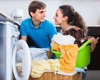 Husband helping housewife to use washing machine indoors Stock Image