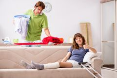 The husband helping leg injured wife in housework. Husband helping leg injured wife in housework royalty free stock images
