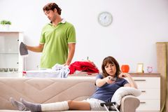 The husband helping leg injured wife in housework stock photography