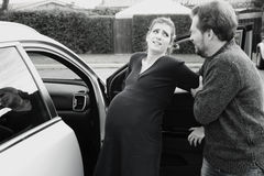 Husband helping pregnant wife to get into car to go to the hospital Stock Photos