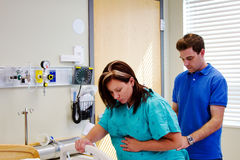 Husband helping wife through labor pain. Husband assisting wife in labor at hospital Stock Image