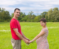 Husband with his pregnant wife. On the green meadows Royalty Free Stock Images