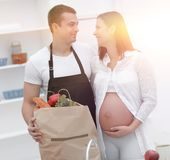 Husband and his pregnant wife are combing through the pack,stand. Ing in the kitchen. concept of family Royalty Free Stock Image