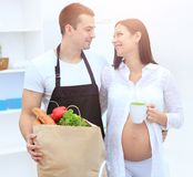 Husband and his pregnant wife are combing through the pack,stand. Ing in the kitchen. concept of family Stock Image