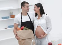 Husband and his pregnant wife are combing through the pack,standing in the kitchen. Concept of family Stock Photo