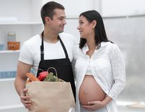 Husband and his pregnant wife are combing through the pack,standing in the kitchen. Concept of family Stock Photos