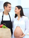 Husband and his pregnant wife are combing through the pack,standing in the kitchen. Concept of family Royalty Free Stock Image