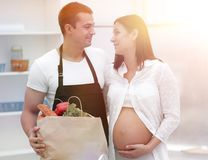 Husband and his pregnant wife are combing through the pack,standing in the kitchen. Concept of family Stock Image