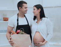 Husband and his pregnant wife are combing through the pack,standing in the kitchen. Concept of family Stock Images