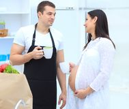 Husband and his pregnant wife with a Cup of cocoa standing in the kitchen. Concept of family life Royalty Free Stock Photos