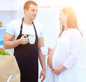 Husband and his pregnant wife with a Cup of cocoa standing in th. E kitchen. concept of family life Stock Photography