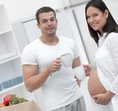 Husband and his pregnant wife drinking cocoa ,standing in the kitchen. Concept of family Stock Photos