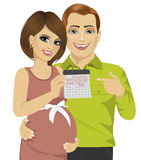 Husband and his pregnant wife pointing to calendar Royalty Free Stock Images