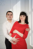 Husband and his pregnant wife in a red dress Royalty Free Stock Photo