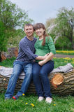 Husband and his pregnant wife sitting on a wooden deck.  Royalty Free Stock Image