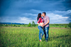 Husband and his pregnant wife are walking at sunse. T in field on the outside Royalty Free Stock Photography