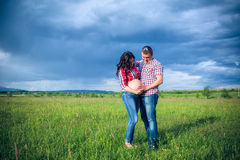 Husband and his pregnant wife are walking at sunse. T in field on the outside Stock Image