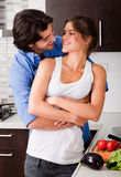Husband hold is wife. In the kitchen and about to kiss stock photos