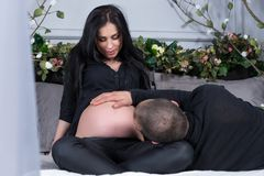 Husband holding his hand on his pregnant wife`s belly while lyin Stock Images