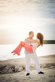Husband holding wife in his arms on the beach royalty free stock photos