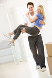 Husband holding wife in new home smiling Royalty Free Stock Photos
