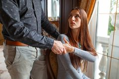 The husband holds his wife by the hand, by the window. royalty free stock photos