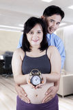 Husband holds pregnant tummy with clock Stock Image