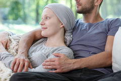 Husband hugging wife with cancer. Young husband hugging wife with cancer happy because of remission Stock Image