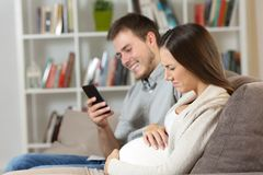 Husband ignoring his pregnant wife suffering Royalty Free Stock Photo
