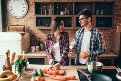Husband juggles oranges while wife cooking. Young husband juggles oranges on the kitchen while wife cooking fruit breakfast. Man and women preparing vegetable Royalty Free Stock Images