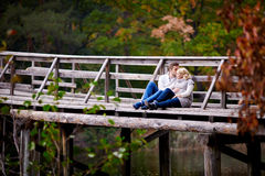 Husband kisses his pregnant wife sitting on a wooden bridge.  Royalty Free Stock Photo